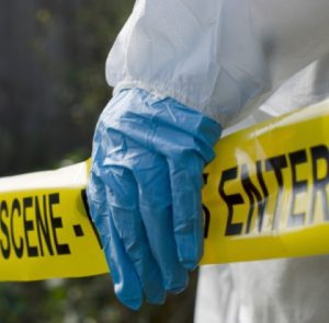 Crime scene tape and a man with a hazmat suit on