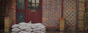 Sandbags blocking water at the front door of a home