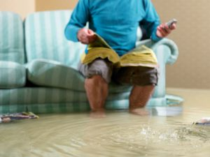 Man sitting in flooded living room